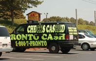 Cash and evidence seized during an investigation into the illegal activities of Pronto Cash, a Florida business, that used mobile check-cashing vans pictured above, indicted for operating an unlicensed money service.