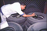 Havana: A local health worker uses a torch to check for signs of water and mosquito eggs inside tyres in a tyre depot.