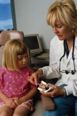 Fotografía de una dentista enseñándole a una niña cómo cepillarse los dientes
