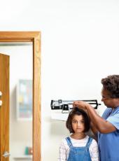 Fotografía de una enfermera midiendo la estatura de una niña