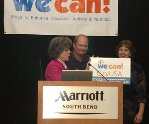 Image of Karen Donato presenting We Can City Sign to recipients in South Bend