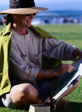 Photograph of a woman in a hat and sunglasses drawing in a park