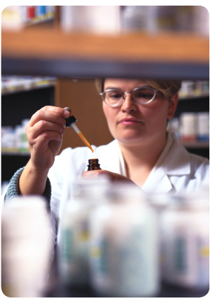 photo of pharmacist in the back area of a pharmacy, adding a liquid to the contents of a small glass bottle with an eye dropper,