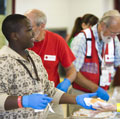 San Antonio, TX.  Raymond McGee, age 13, helps the Red Cross volunteers serve lunch at the shelter where he is staying.