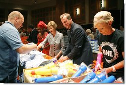Mrs. Laura Bush, joined by Mrs. Cindy McCain, right, help HIV and AIDS advocate Princess Kasune Zulu, left, and One Chairman and CEO David Lane assemble care-giver packages at the ONE campaign event Tuesday, Sept. 2, 2008 at the Minneapolis Convention Center in Minneapolis, in support of health care workers who treat AIDS paitients in African countries.  White House photo by Shealah Craighead