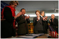 Laura Bush applauds as Secretary of Education Margaret Spellings and Afghan Minister of Education Noor Mohammas Qarqeen complete the signing of the Memorandum of Understanding for funds to build a university in Kabul, Afghanistan, Wednesday, March 30, 2005.