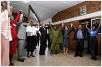 President George W. Bush, Mrs. Laura Bush, and to the President's right, Ugandan President Yoweri Museveni and Mrs. Museveni sing along with a choir and staff members of The AIDS Support Organization (TASO) Centre in Entebbe, Uganda Friday, July 11, 2003.