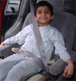 child properly restrained in a booster seat and seatbelt