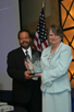 a photo of NIBIB Director Dr. Roderic Pettigrew presenting an award to M. Joan Dawson