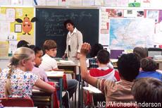 Photograph of a teacher and children in a classroom