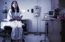Fotografía de una paciente vestida con una bata y sentada en un cuarto de exámen del hospital