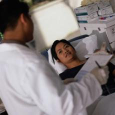Photograph of a male healthcare professional talking to a woman in a hospital bed