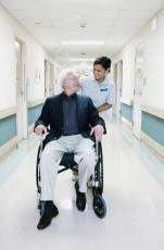 Photograph of a female nurse pushing a senior man in a wheelchair