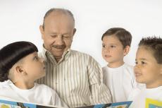 Photograph of a senior man reading a book to three young boys