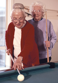 Two older women playing biliards.
