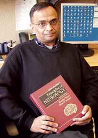FDA neurologist and medical reviewer Dr. Ranjit Mani, M.D., sitting at his desk holding a neurology text book.