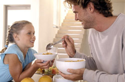 man and girl eating cereal
