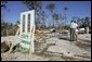 President George W. Bush stands with Al Boyd in the ruins of where Boyd's home used to be during a walking tour of neighborhoods damaged by Hurricane Ivan in Pensacola, Florida, Sunday, Sept. 19, 2004.  White House photo by Eric Draper