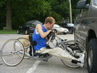 Photo of a young man on a handcycle, checking his gear.