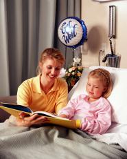 Fotografía de una mujer leyéndole a una niña acostada en una cama de hospital