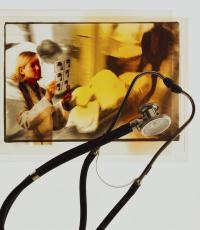 Photograph of a stethoscope with a doctor and a critically ill patient in the background