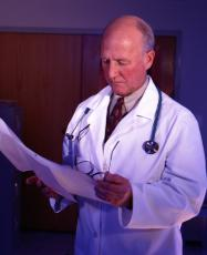 Photograph of a male doctor looking at a chart
