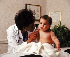 Photograph of a female doctor examining a baby
