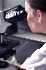 Photograph of a female scientist looking through a microscope