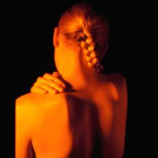 Photograph of a woman holding her shoulder in pain