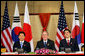 President George W. Bush sits with President Roh Moo-Hyun, of the Republic of Korea, left, and Japan's Prime Minister Shinzo Abe during a trilateral discussion Saturday, Nov. 18, 2006, at the Sheraton Hanoi hotel in Hanoi, where they are participating in the Asia Pacific Economic Cooperation summit. White House photo by Eric Draper