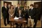 President George W. Bush signs S. 2634, the Garrett Lee Smith Memorial Act, in the Roosevelt Room Thursday, Oct. 21, 2004. The act authorizes the spending of $82 million for youth suicide prevention programs at college campus mental health centers. The legislation is named for Garret Smith, the son of Sen. Gordon Smith, R-Ore., and Sharon Smith, who are standing directly behind the President. Their son committed suicide Sept. 8, 2003.  White House photo by Paul Morse