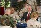 President George W. Bush sits down for lunch with military personnel at MacDill Air Force Base in Tampa, Florida, Wednesday, March 26, 2003.  White House photo by Paul Morse