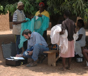 Steve Smith, CDC chemist, uses a portable X-ray fluorescence analyzer to measure the insecticide content of a treated bed net in rural Ghana. (Courtesy Joel Selanikio, DataDyne).