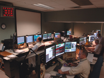 people sitting in front of computers in the Space Telescope Operations Control Center