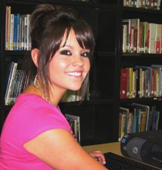 Image of Morgan J sitting in front of a school library computer workstation