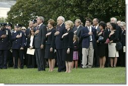 President George W. Bush, Mrs. Bush, Vice President Dick Cheney and Mrs. Cheney, stand by families of victims of 911 during the playing of Taps following a Moment of Silence on the South Lawn, Saturday, Sept. 11, 2004.  White House photo by David Bohrer