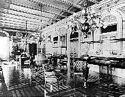 Black and white photo of the Vice President's Office featuring two chairs, a desk, a chandelier and ornate wall stenciling.