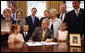 President George W. Bush is joined at his desk by Hannah Lewis, age 7, left, Wyatt Rech, age 6, Eden Adams, age 8, right, Mrs. Laura Bush, other family members, and Sen. Norm Coleman R-MN; Rep. Deborah Pryce R-OH; and Rep. Chris Van Hollen D-MD; Tuesday, July 29, 2008, after signing the Caroline Pryce Walker Conquer Childhood Cancer Act of 2008 in the Oval Office of the White House. White House photo by Eric Draper