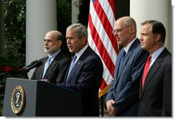 """President George W. Bush stands with Federal Reserve Chairman Ben Bernanke, left, SEC Chairman Chris Cox, right, and Treasury Secretary Hank Paulson as he delivers a statement on the economy Friday, Sept. 19, 2008, in the Rose Garden of the White House. Said the President, """"This is a pivotal moment for America's economy. We must act now to protect our nation's economic health from serious risk.""""  White House photo by Joyce N. Boghosian"""