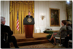 """President George W. Bush addresses the White House Conference on Preparing Tomorrow's Teachers in the East Room March 4, 2002. Pictured in the audience from left to right is U. S. Sen. Edward Kennedy (D-Mass.), Laura Bush and Lynne Cheney. """"We're focusing much of the teacher training effort on specific needs, like special education or math or science, and one of my passions, early reading,"""" said the President. """"The Reading First program is aimed at making sure every child of every background can read by the third grade."""" White House photo by Eric Draper."""