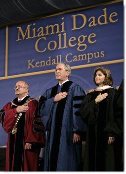 President George W. Bush stands for the national anthem onstage at Miami Dade College - Kendall Campus in Miami Saturday, April 28, 2007, before delivering the 2007 commencement address. With him are Miami Dade College President Dr. Eduardo Padron and Helen Aquirre Ferre, Chairman of the Board of Trustees at Miami Dade College. White House photo by Eric Draper