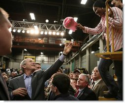 President George W. Bush reaches up to grab a worker's cap to autograph it during his tour of the Caterpillar Inc. facility in East Peoria, Ill., Tuesday, Jan. 30, 2007.  White House photo by Paul Morse