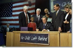 Visiting Hamilton High School in Hamilton, Ohio, Jan. 8, President George W. Bush signs into law historic, bi-partisan education legislation. On hand for the signing are Democratic Rep. George Miller of California (far left), Democratic U.S. Sen. Edward Kennedy of Massachusetts (center, left), Secretary of Education Rod Paige (center, behind President Bush), Republican Rep. John Boehner of Ohio, and Republican Sen. Judd Gregg of New Hampshire (not pictured).  White House photo by Paul Morse
