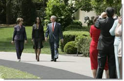 """President George W. Bush and Mrs. Laura Bush accompany 2006 National Teacher of the Year Kim Oliver to the South Lawn ceremony in her honor Wednesday, April 26, 2006. Said the President of the Silver Spring, Maryland kindergarten teacher, """"Kim Oliver understands that the key to helping children succeed is fighting the soft bigotry of low expectations."""" White House photo by Paul Morse"""