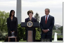 Mrs. Laura Bush addresses the audience Wednesday, April 26, 2006, as President Bush and Kim Oliver, the 2006 National Teacher of the Year, look on during a ceremony on the South Lawn honoring Ms. Oliver and the State Teachers of the Year.  White House photo by Paul Morse
