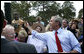 President George W. Bush reaches up to shake the hand of a youngster Tuesday, May 29, 2007, after delivering remarks on comprehensive immigration reform during a visit to the Federal Law Enforcement Training Center in Glynco, Ga. White House photo by Eric Draper