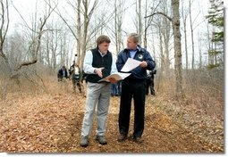 President George W. Bush looks over maps of the Wells National Estuarine Research Reserve with Manager Paul Dest in Wells, Maine, Thursday, April 22, 2004.  White House photo by Eric Draper