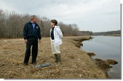 """President George W. Bush on speaks with Research Director Dr. Michele Dionne during a tour of the Wells National Estuarine Research Reserve in Wells, Maine, Thursday, April 22, 2004. """"Up to half of all North American bird species nest or feed in wetlands. About half of all threatened and endangered species use wetlands. There's some endangered species using the wetlands right here on this piece of property,"""" said the President in his remarks.  White House photo by Eric Draper"""