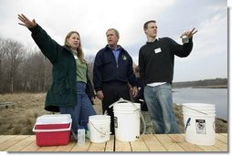 """President George W. Bush participates in a water testing project with Education Director Laura Lubelczyk, left, and volunteer Trak Lord at the Wells National Estuarine Research Reserve with in Wells, Maine, Thursday, April 22, 2004. In his remarks, President Bush discussed the value of volunteering in places like the reserve, """"But what makes this beautiful part of the world go is the 400 volunteers who work here -- the 400 volunteers who are exercising their responsibility as citizens to make this beautiful part of the world even more beautiful and more meaningful.""""  White House photo by Eric Draper"""