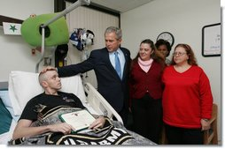 President George W. Bush visits with U.S. Army Sgt. John Wayne Cornell of Lansing, Mich., after presenting him with a Purple Heart Thursday, Dec. 20, 2007, during a visit to Walter Reed Army Medical Center in Washington, D.C., where he is recovering from injuries suffered in Operation Iraqi Freedom. With them are Sgt. Cornell's wife, Dee, and mother-in-law Diane Elaine Galloway. White House photo by Joyce N. Boghosian